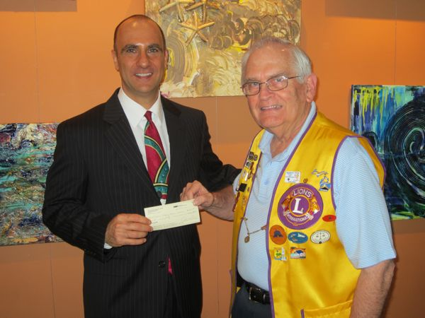 Library Director Alan Kornblau receives the $500 check from Lions Club Treasurer John Parke.